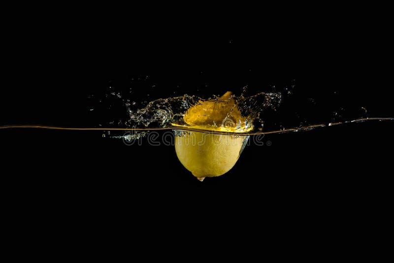 Citron dans l'eau sur un fond foncé image libre de droits