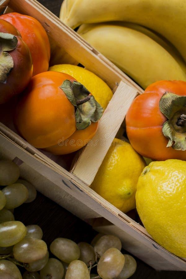 Citron för druvabananpersimoner i en korg arkivfoto