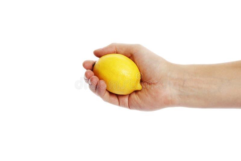 Citron i handen som isoleras på en vit bakgrund arkivfoton