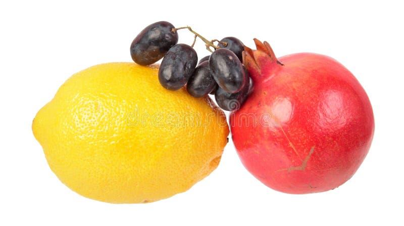 Citron jaune, grenade rouge et raisins mûrs pourpres foncés d'isolement sur le fond blanc Ingrédients pour la salade photographie stock