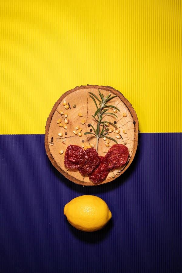 Citron med torkat - frukt på en guling och en purpurfärgad bakgrund arkivbilder