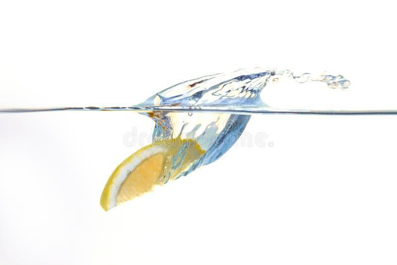 Citron tombant dans l'eau avec une éclaboussure photos libres de droits