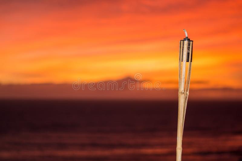 Citronella oil lamp burning at sunset royalty free stock photo