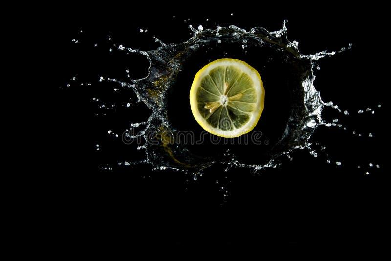 Citronen tappas in bevattnar färgstänk royaltyfria foton