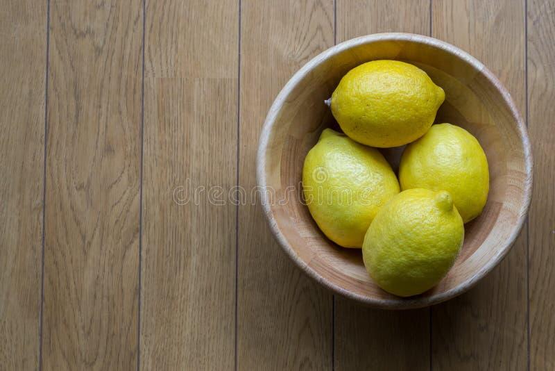 Citroner i en träkopp på den wood tabellen royaltyfria bilder