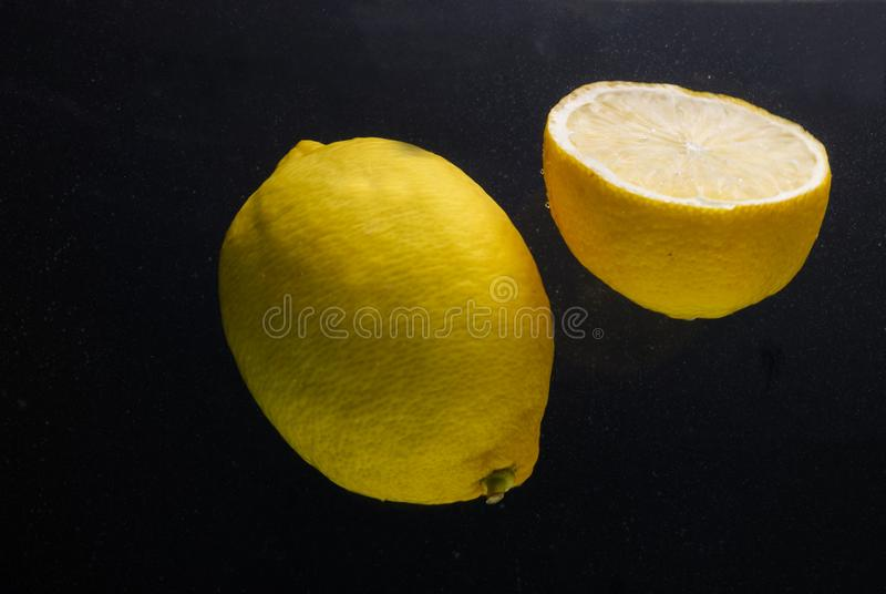 Citroner i vatten på en svart bakgrund arkivbild