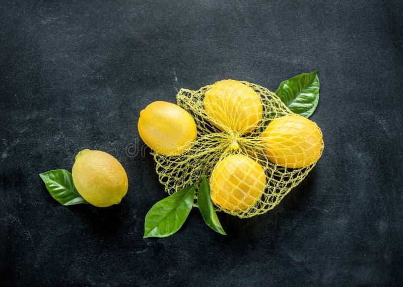 Citroner med nya sidor på den svarta svart tavlan arkivbilder