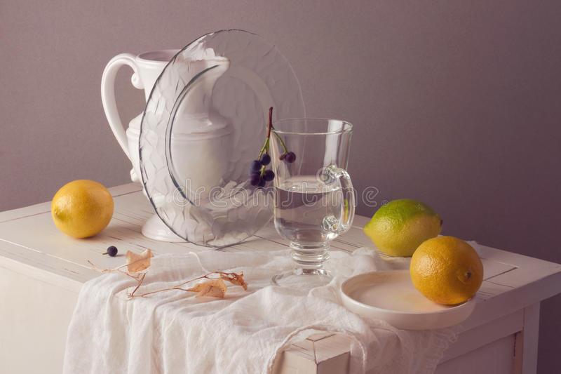 Citroner och exponeringsglas av vatten på tabellen Lantlig stillebensammansättning fotografering för bildbyråer