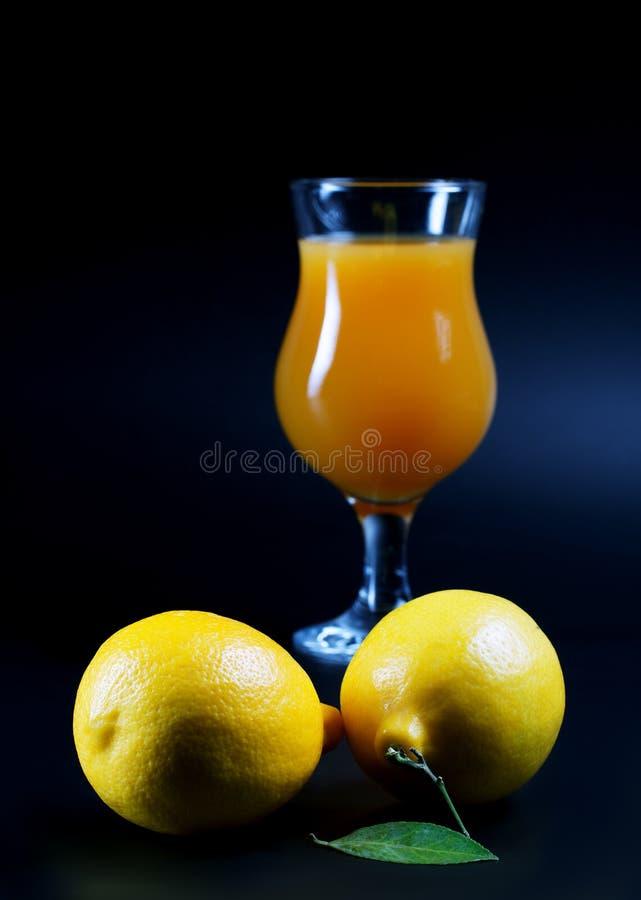 Citroner och fruktsaftexponeringsglas på en svart arkivfoto