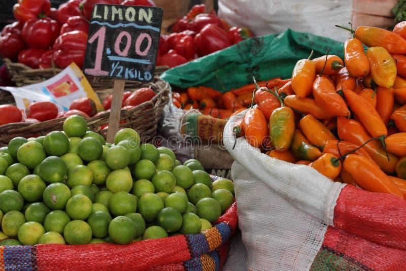 Citroner och guling pepprar till salu i populär marknad royaltyfri foto