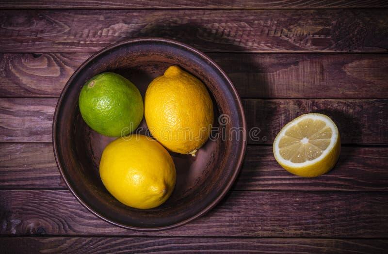 Citroner och limefrukt på mörk träbakgrund royaltyfria bilder