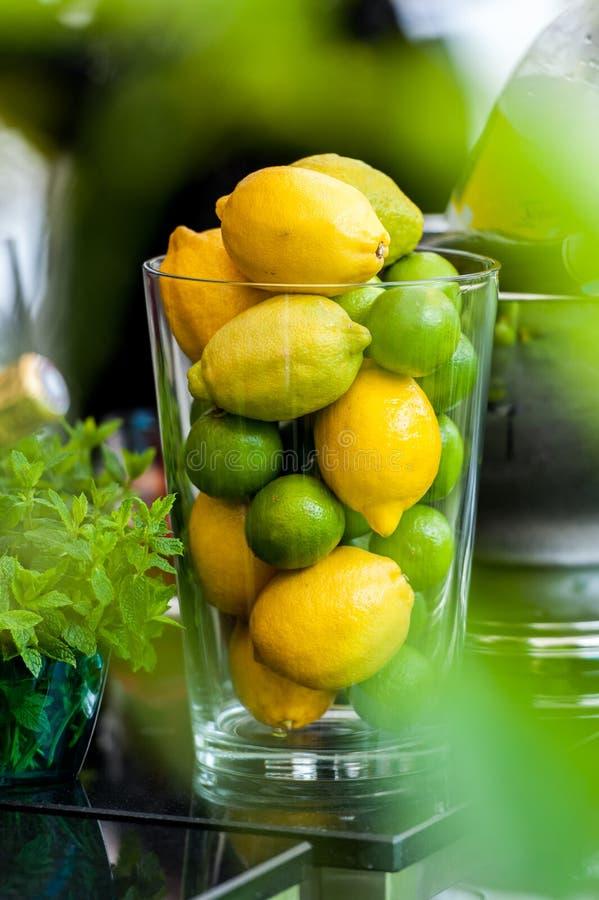 Citroner och limefrukter i ett exponeringsglas arkivfoton