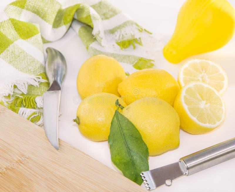Citroner, press, Zester, kniv och träskärbräda arkivfoto