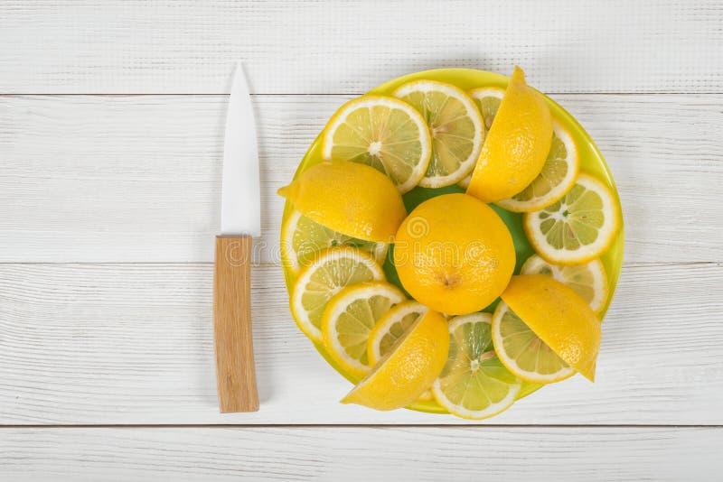 Citronfreder som ut läggas runt om den hela citronen på ett bräde royaltyfria foton