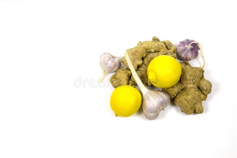 Citroningefäran rotar vitlök på vit bakgrund Användbara produkter för hjärtan och blodkärlen arkivbilder