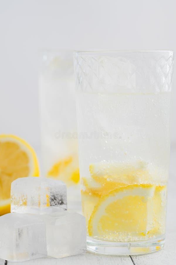 Citronjuicedetoxvatten Mineralvatten som inges med citroner Trävit tabell royaltyfri bild