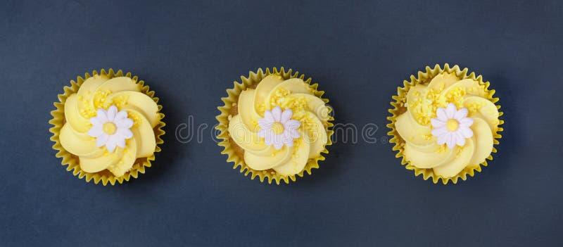 Citronmuffin med den smörkrämvirvel och fondanten blommar garnering royaltyfri foto