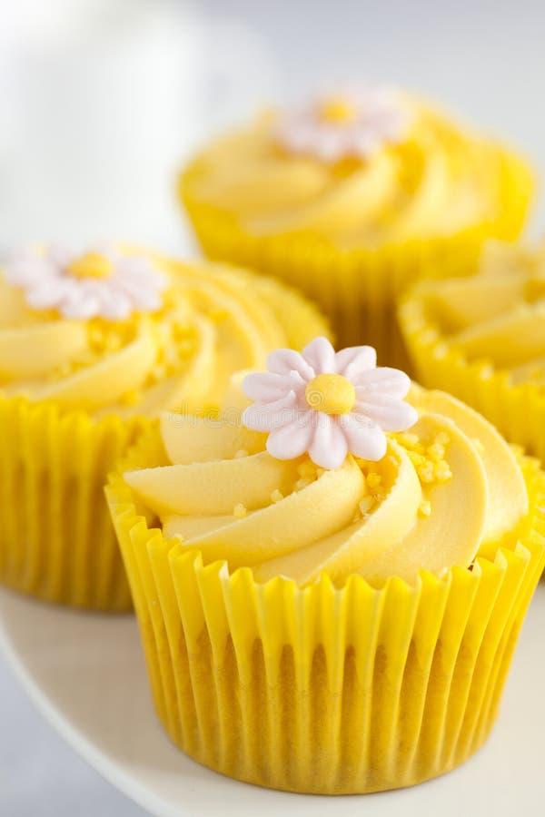 Citronmuffin med den smörkrämvirvel och fondanten blommar garnering royaltyfria bilder