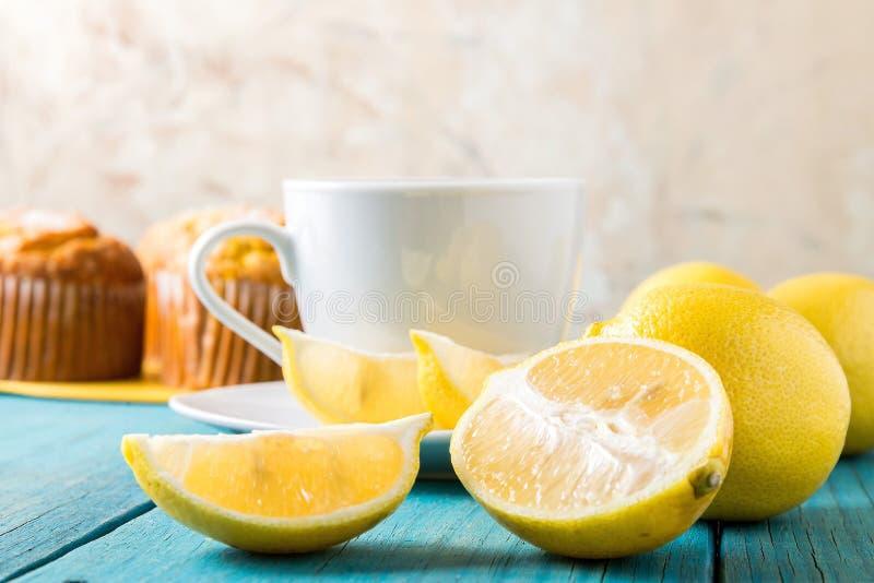 Citronmuffin med kopp te/kaffe fotografering för bildbyråer