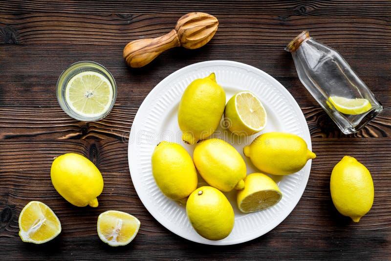 Citronnade faite maison fraîche Citrons, presse-fruits, verre pour la boisson sur la vue supérieure de fond en bois foncé photo libre de droits