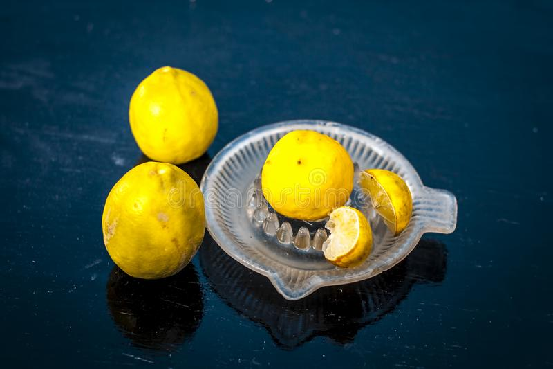 Citrons avec le presse-fruits de citron sur la surface en bois images stock