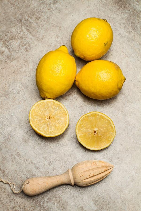 Citrons et presse-fruits en bois photos stock