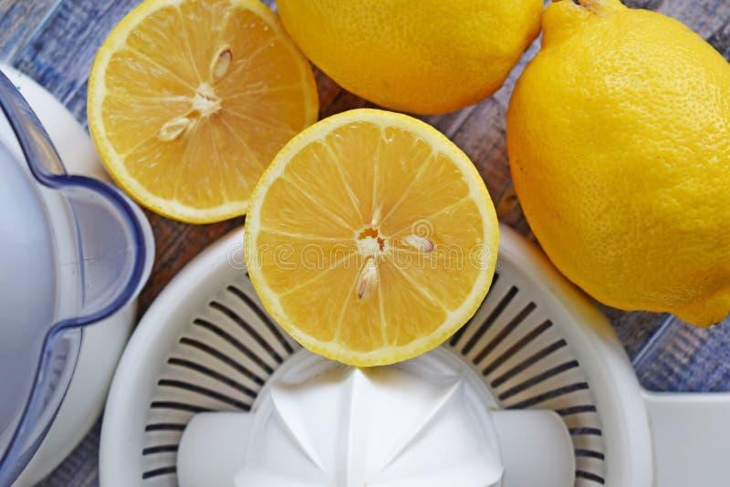 Citrons et presse-fruits frais d'agrume sur le fond en bois image libre de droits