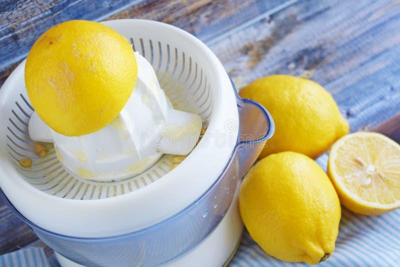 Citrons et presse-fruits frais d'agrume sur le fond en bois images libres de droits
