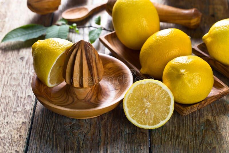 Citrons et vieux presse-fruits en bois images stock