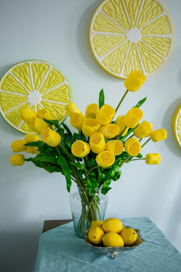 Citrons jaunes et tulipes jaunes sur la table photos stock