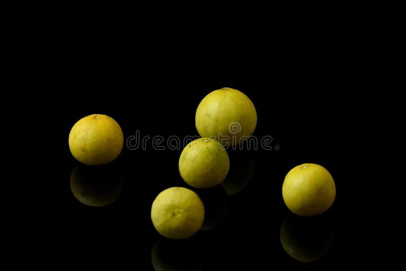 Citrons jaunes sur le fond d'isolement noir image stock