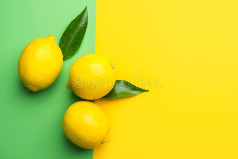 Citrons organiques mûrs lumineux sur le fond de duotone de contraste de la combinaison du vert jaune Nourriture cr?atrice Boisson photographie stock libre de droits