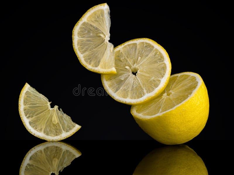Citronskivor, stycken på en svart bakgrund ovanligt foto Verka för att trotsa gravitation royaltyfri foto