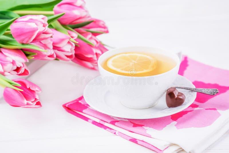 Citronte, chokladhjärta, rosa magentafärgade tulpanblommor på vit träbakgrund arkivbilder