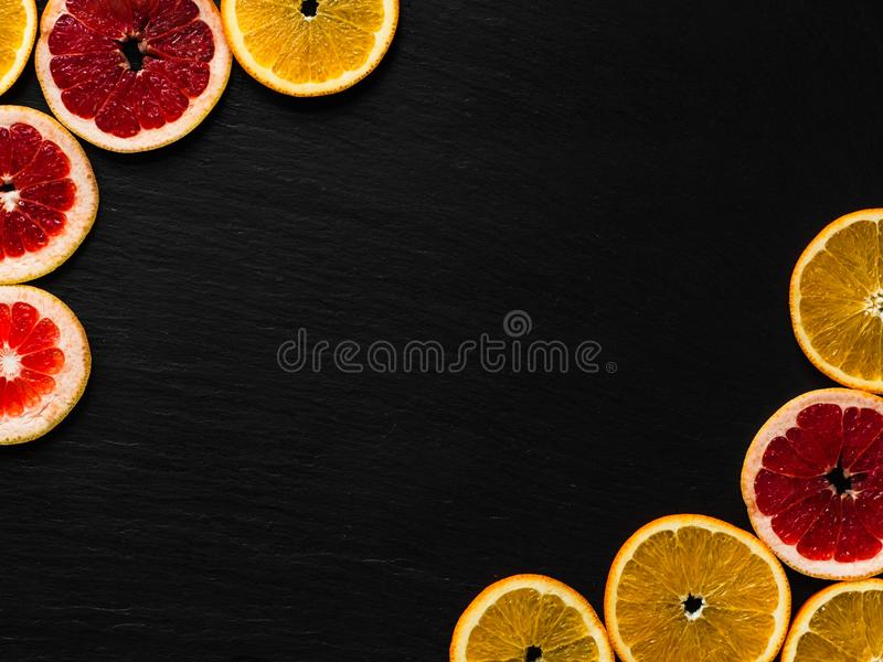 Citrus frame template on black texturised background. Photo with orange and grapefruit slices in corners. Fruit flatlay with place royalty free stock images