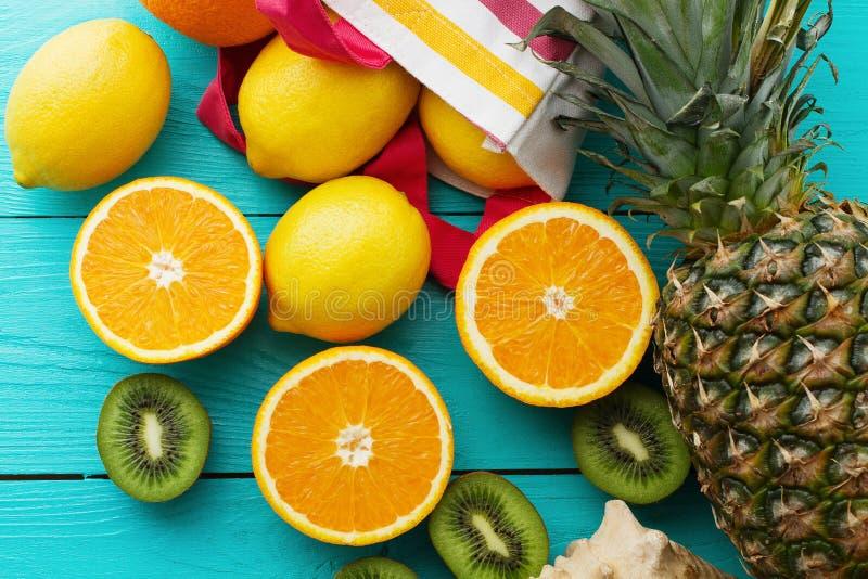 Citrus fresh food. Summer holidays. Orange, kiwi, pineapple, lemon and sea shell on blue wooden background. Vacation. Citrus fresh food. Summer holidays. Orange royalty free stock photography