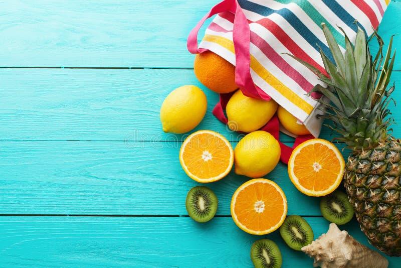 Citrus fresh food. Summer holidays. Orange, kiwi, pineapple, lemon and sea shell on blue wooden background. Vacation. Citrus fresh food. Summer holidays. Orange royalty free stock images