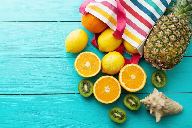 Citrus fresh food. Summer holidays. Orange, kiwi, pineapple, lemon and sea shell on blue wooden background. Vacation and summer. Citrus fresh food. Summer royalty free stock photos