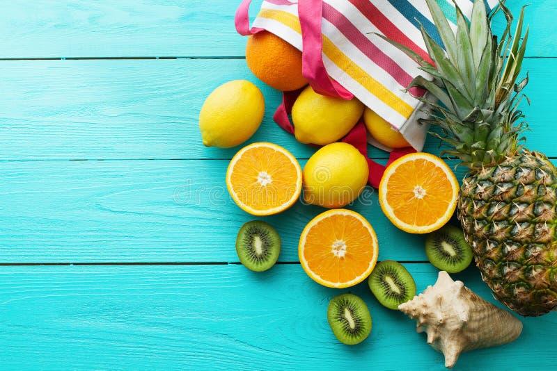 Citrus fresh food. Summer holidays. Orange, kiwi, pineapple, lemon and sea shell on blue wooden background. Vacation summertime. Citrus fresh food. Summer stock image