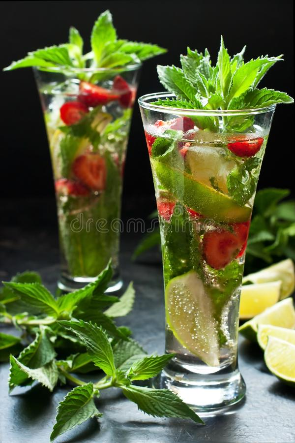 Citrus fruit cocktail with   mint, lime and strawberry  in glass royalty free stock image