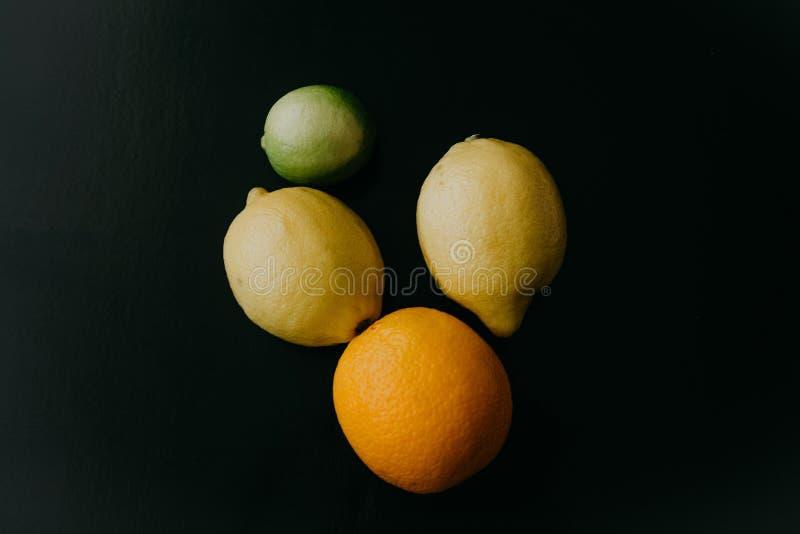 Citrus or fruit mix of orange, lemon and lime on a black background royalty free stock photo