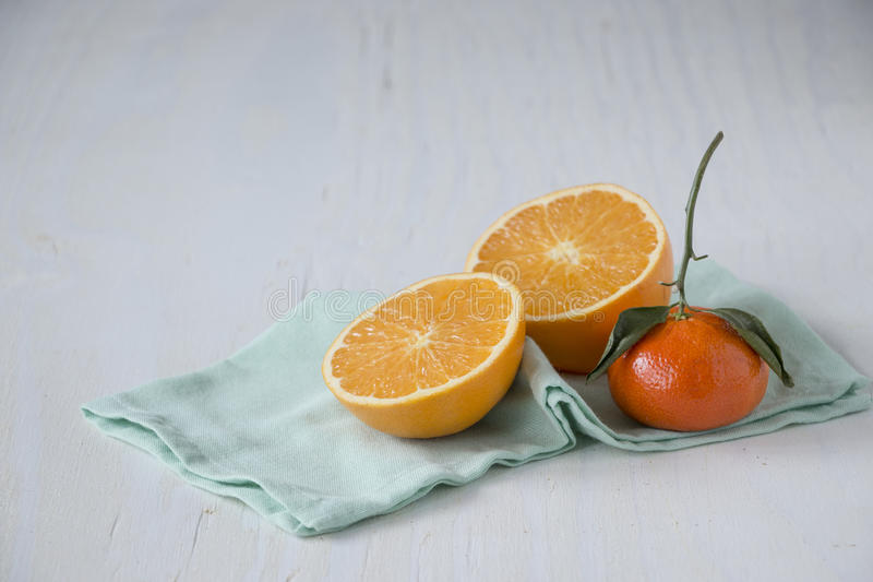 Citrus fruit. Seasonal produce. Orange in halves and one mandarines on light blue cloth over white wooden table. Seasonal produce from winter. Healthy symbol royalty free stock photos