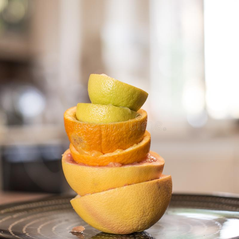 Citrus fruit squeezed in the kitchen stacked peels to form a tow. Citrus fruit squeezed into the kitchen stacked peels to form a tower on a black plate stock image