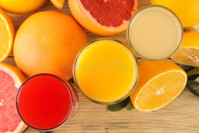 Citrus fruit. various citrus fruits with leaves of lemon, orange, grapefruit and juices on a natural wooden table. top view stock photo