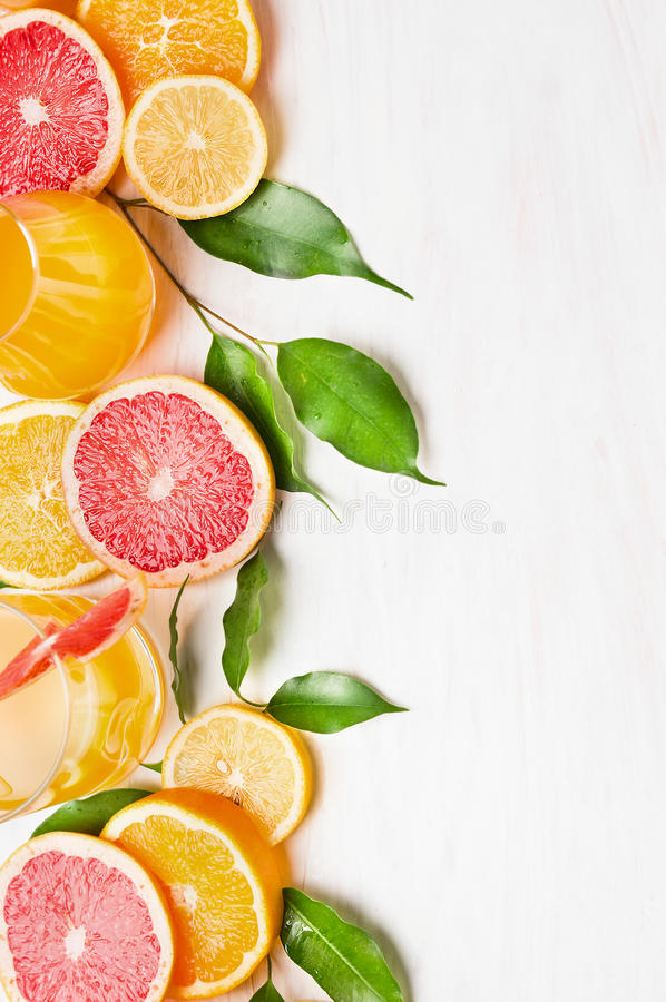 Citrus fruits with green leaves and glass with juice on white wooden table , frame. With place for text royalty free stock photo