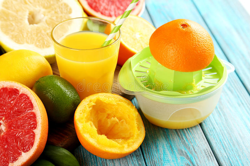 Citrus fruits. With juicer on a blue wooden table royalty free stock photos
