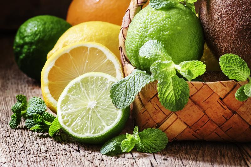 Citrus fruits, kiwi and mint leaves in a wicker basket, vintage stock photo