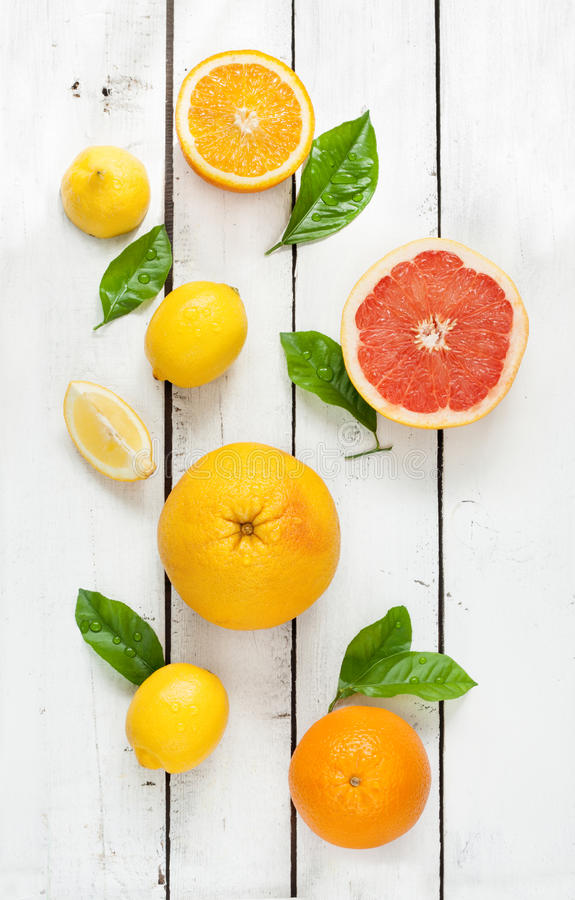 Citrus fruits (lemon, grapefruit and orange) on white wood. Citrus fruits (lemon, grapefruit and orange) with fresh wet leaves on white wooden table - still life stock photos