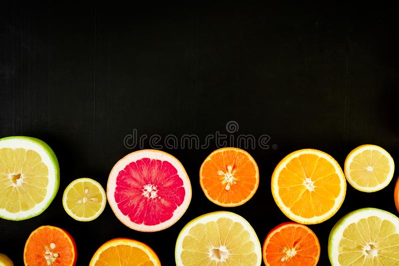 Citrus fruits - lemon, orange, grapefruit, sweetie and pomelo on black background. Juicy concept. Flat lay, top view. stock photography