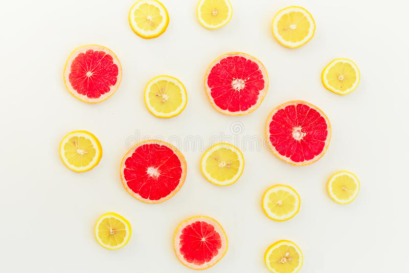 Citrus fruits pattern of lemon and grapefruit on white background. Flat lay, top view. Fruit`s background. Citrus fruits pattern of lemon and grapefruit on white stock image